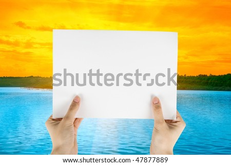 Hand holding white paper at beauty sunset on river background - stock photo