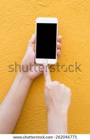 Hand holding white Smart-phone on yellow wall background - stock photo