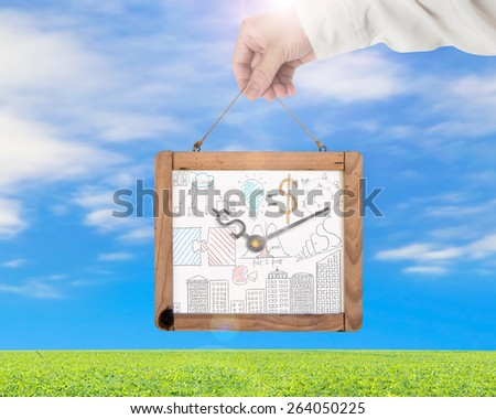 Hand holding whiteboard of dollar sign clock with business concept doodles on blue sky clouds green grass background. Time is money concept. - stock photo
