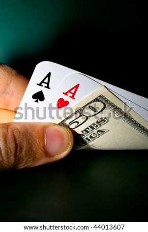 Hand holding winning cards and dollar - stock photo