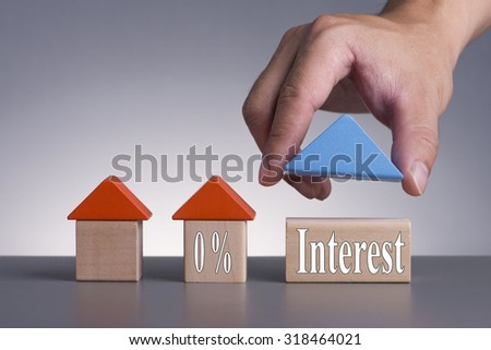 Hand holding wooden house (Housing Loan Concept) with word 0% Interest - stock photo