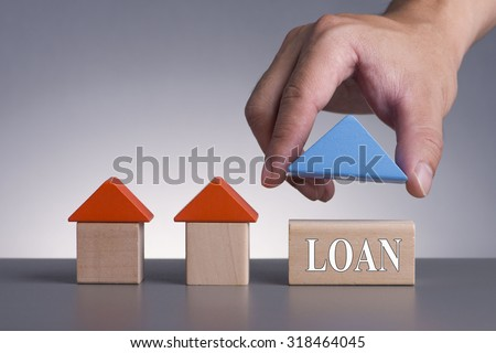 Hand holding wooden house (Housing Loan Concept) with word Loan - stock photo
