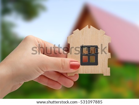 Hand holding wooden panel prefabricated house in the background of summer landscape with house. Dream house.