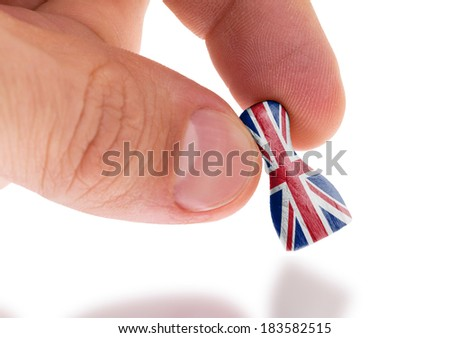 Hand holding wooden pawn with a flag painting, selective focus, United Kingdom - stock photo
