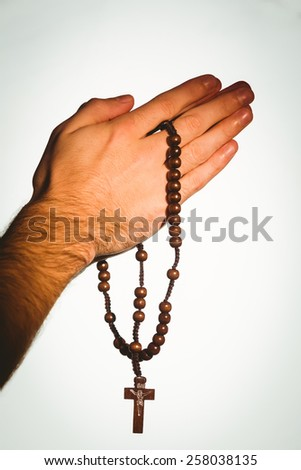 Hand holding wooden rosary beads on white background - stock photo