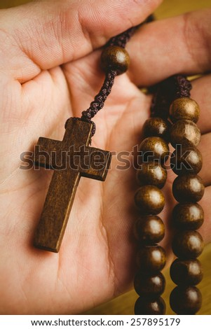 Hand holding wooden rosary beads overhead shot - stock photo