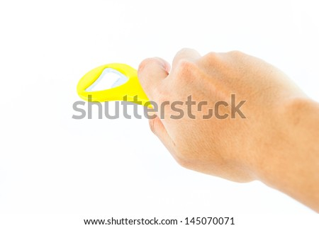 Hand holding yellow bottle opener isolated on white background - stock photo