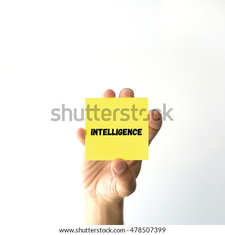 Hand holding yellow sticky note written INTELLIGENCE word