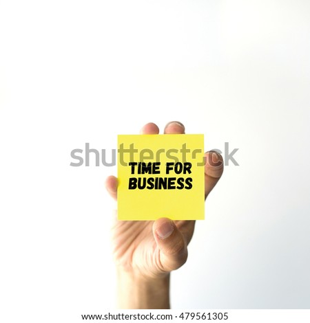 Hand holding yellow sticky note written TIME FOR BUSINESS
