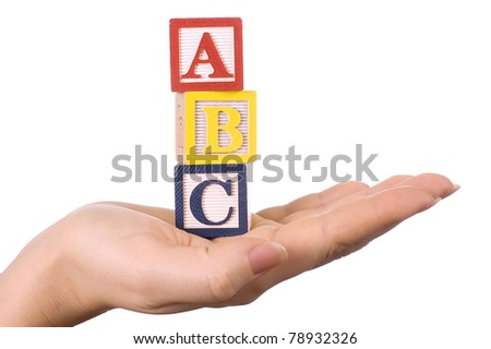 Hand holds a cube with letters - stock photo