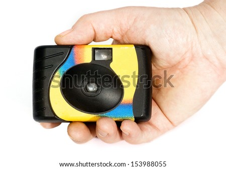 hand holds a disposable film camera 35mm retro. - stock photo