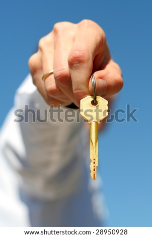 hand holds a gold key (key in focus)