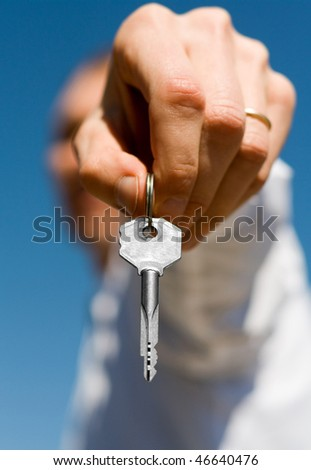 hand holds a gold key (key in focus) - stock photo