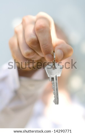 hand holds a key (key in focus) - stock photo