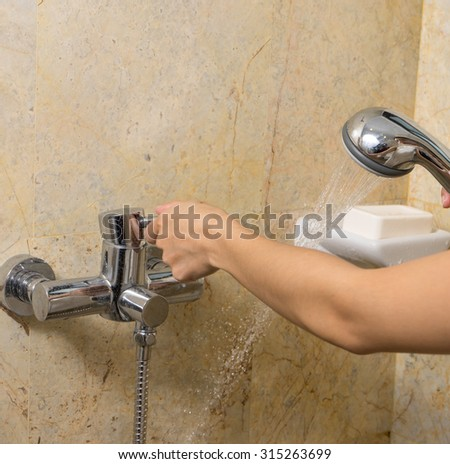 Hand holds a shower on marbles background