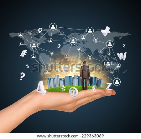 Hand holds city of skyscrapers on green grass and businessman walking forward. Flying letters and network with people icons near hand. Business concept - stock photo
