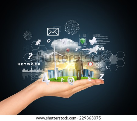Hand holds city of skyscrapers on green grass and businessman walking forward. Flying virtual elements near hand. Business concept - stock photo