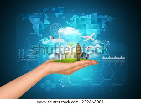 Hand holds city of skyscrapers on green grass and businessman walking forward. World map and hexagons as backdrop. Business concept - stock photo