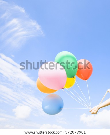 Hand holds colorful balloons - stock photo