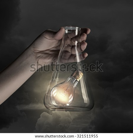 Hand holds flask with glass light bulb inside - stock photo