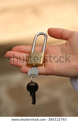 Hand holds lock with key in.