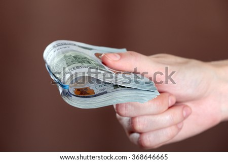 Hand holds money on brown background, close up - stock photo