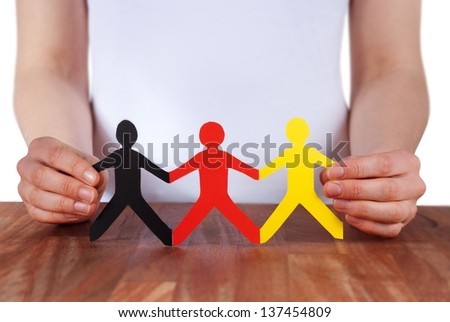 hand holds paper chain people in the color of germany, isolated - stock photo