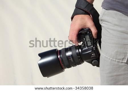 hand holds photo camera and sand - stock photo