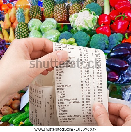 hand holds the check from supermarket - stock photo