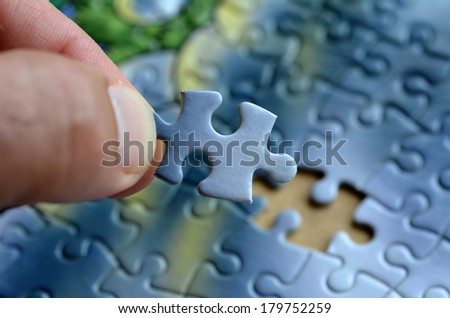 Hand holds the last puzzle piece.Business concept for completing the final puzzle piece - stock photo
