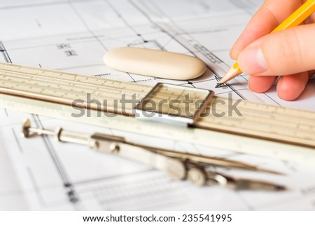 Hand holds the pencil to create a drawing, tools for sketching on the table. Angle view, focus on hand - stock photo