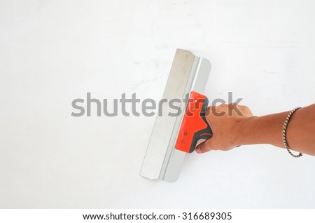 Hand holds trowel have plastered walls, completing the process. The repair composition