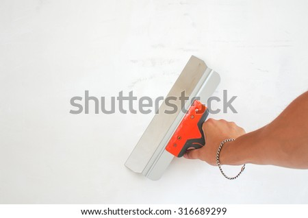 Hand holds trowel plastered around the walls, completing the process. The repair composition - stock photo