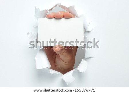 Hand holds white card through white torn paper   - stock photo