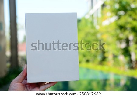 Hand holds white sheet on background - stock photo