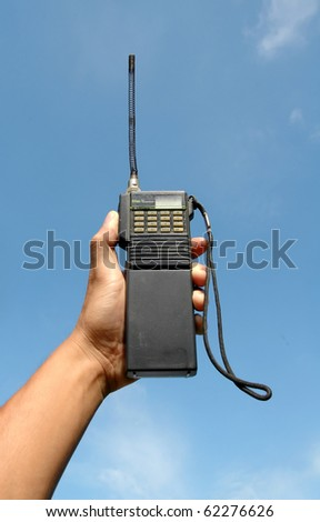 hand hole walky talky with blue sky background - stock photo