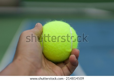 Hand hole yellow tennis ball and serving