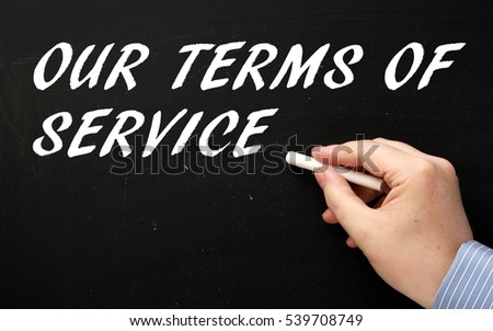 Hand in a business shirt writing the words Our Terms Of Service on a blackboard with a stick of white chalk