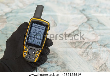 Hand in a glove holding an outdoor GPS over a map of a mountain range. - stock photo