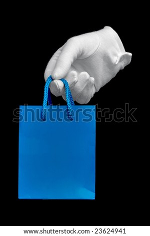 Hand in a white glove holding a small blue shopping bag, isolated on black. - stock photo