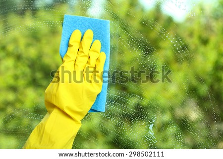 Hand in a yellow glove  wiping soap window with napkin  on the background of trees