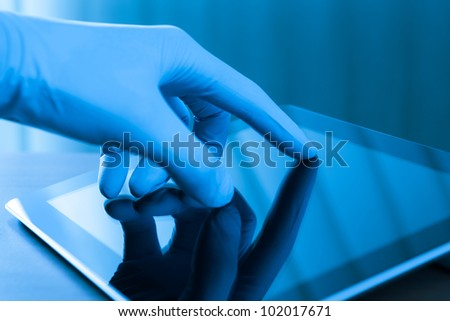 Hand in blue glove touching modern digital tablet. Concept image on medical or research theme. - stock photo