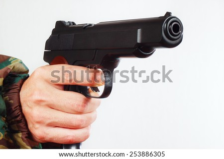 Hand in camouflage uniform with a semi-automatic army handgun close up - stock photo
