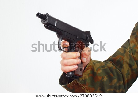 Hand in camouflage uniform with discharged pistol on a white background - stock photo
