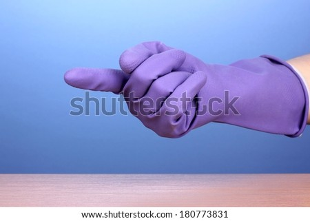 Hand in color cleaning glove holding finger over surface of wooden table on blue background - stock photo