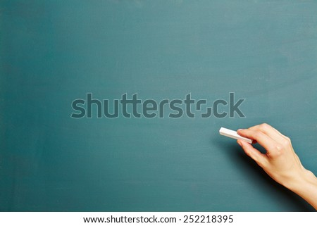 Hand in front of clean green chalkboard