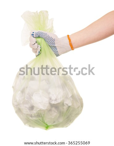 Hand in glove holding a bag of garbage on white background - stock photo