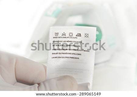Hand in glove holding clothes label with cleaning instructions on a steam iron background. Close up. - stock photo