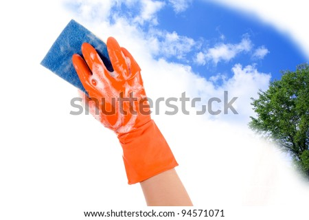 Hand in glove with sponge to clean the sky clears and the green - stock photo