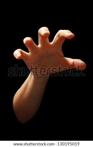 hand in grabbing position isolated over black background - stock photo